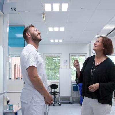 Två sjukhuspersonal i blåvitt dygnsrytmljus.
