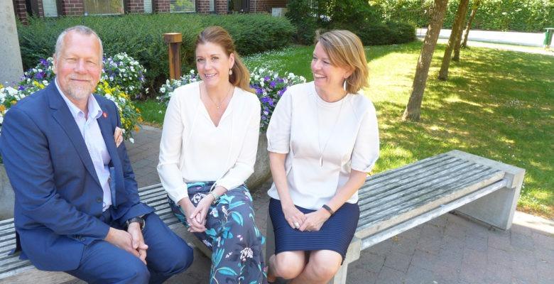Tre chefer som använder Chefoskopet, sittande utomhus på en bänk med grön gräsmatta och kommunhus bakom.