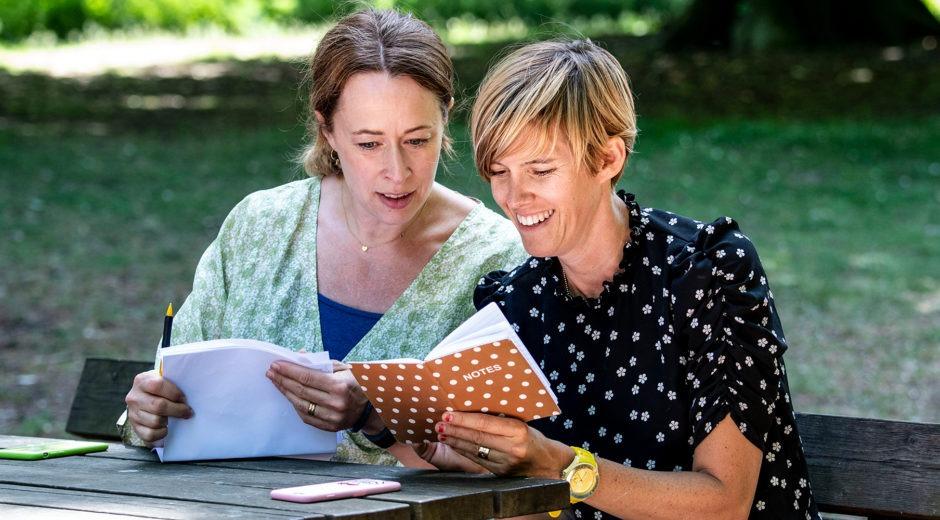 Två bibliotekarier, som ingår i projektet Stick Ut i Malmö., har möte sittande vid ett bord i en park.