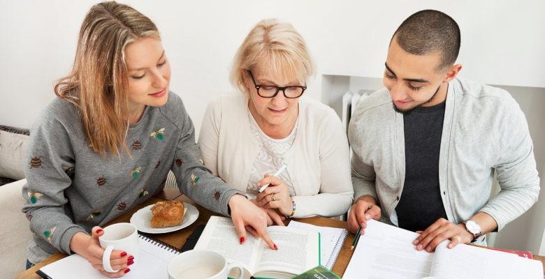 två kvinnor och en man sitter vid bord och går igenom texten på ett papper tillsammans.