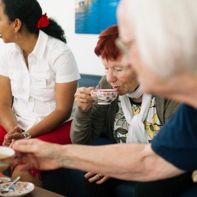 tre kvinnor på ett äldreboende dricker kaffe i en soffa. två äldre och en medelålders.