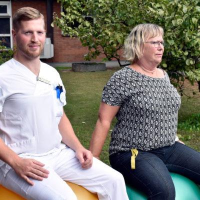 Fysioterapeut och sekreterare sitter på varsin pilatesboll i trädgård utanför vårdcentral, återhämtning i arbetet.