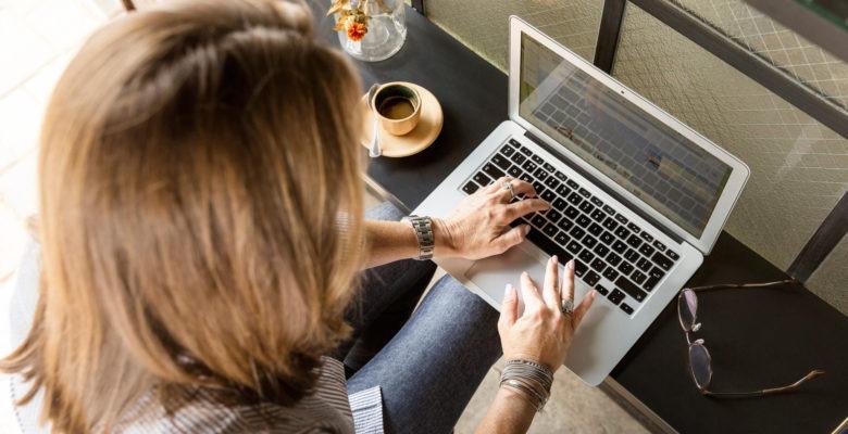 Sittande kvinna skriver på laptop, bättre dokumentation för socialsekreterare.