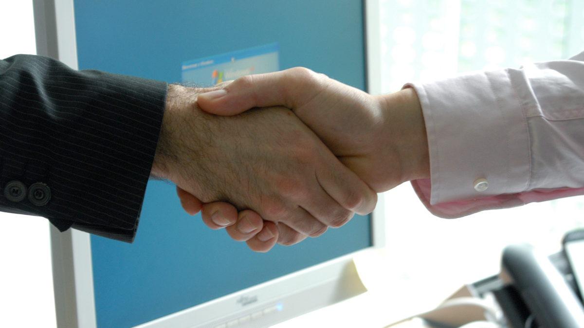 två händer som skakar hand, en med kavajärm, en med skjortärm. bakom händerna syns en dataskärm.