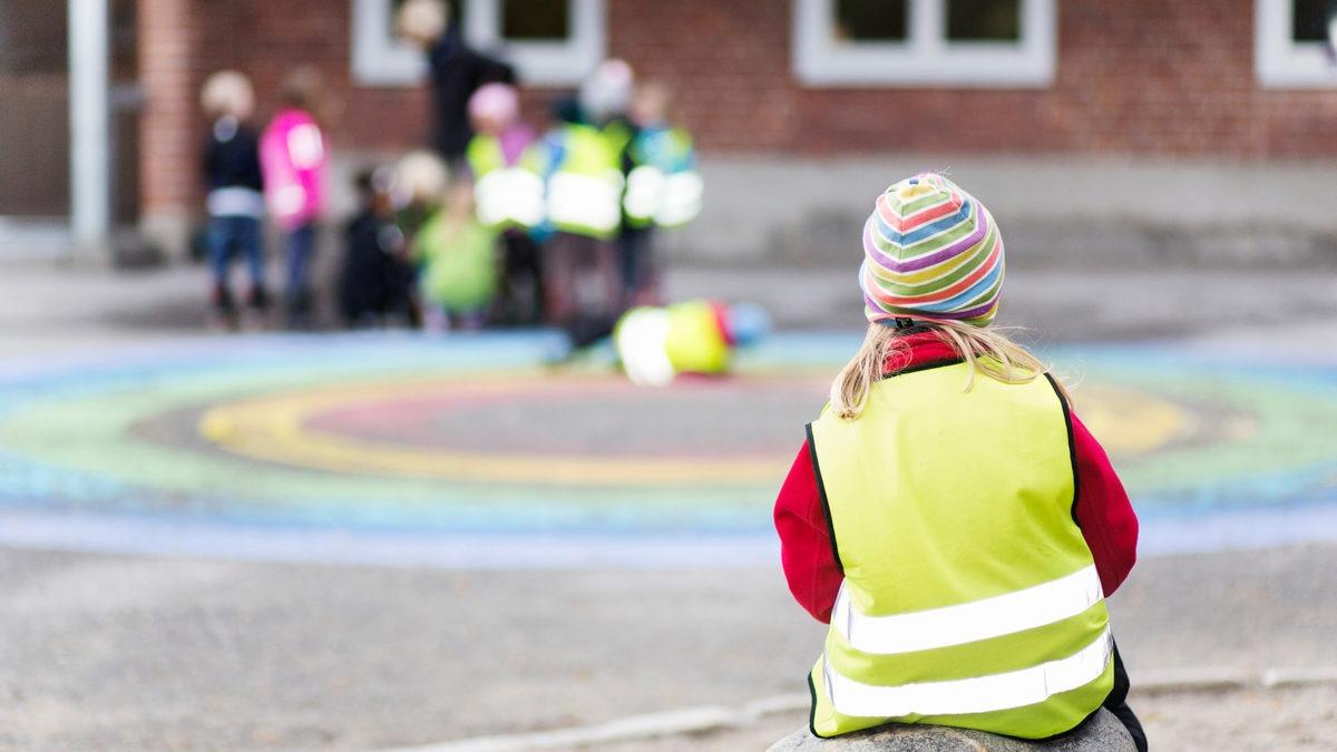 En skolgård. Ett barn med mössa och reflexväst sitter med ryggen mot kameran. I bakgrunden en barngrupp med personal.