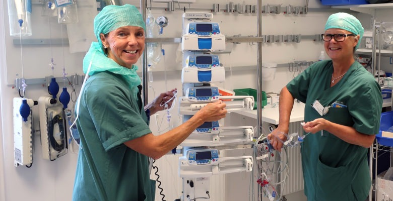 Marika Hasselby Ingmanson och Mia Jensen, i gröna operationskläder, står mitt emot varandra och arbetar med n uppsättning läkemedelspumpar i ett ställ.