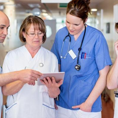 fyra personer i sjukhuskläder står i en sjukhuskorridor och tittar gemensamt i en Ipad som en av dem håller i.