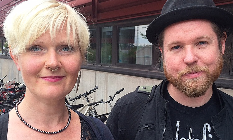 Anna-Carin Fagerlind Ståhl och Christian Ståhl. Anna-Carin i blond page och näsring, Christian i skägg och svart hatt. Står utomhus med ett cykelställ i bakgrunden.