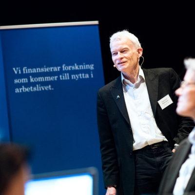 porträtt av Svend Erik Matthiassen, professor i belastningsergonimi. Bakom honom en tavla med reklam för AFA Försäkring