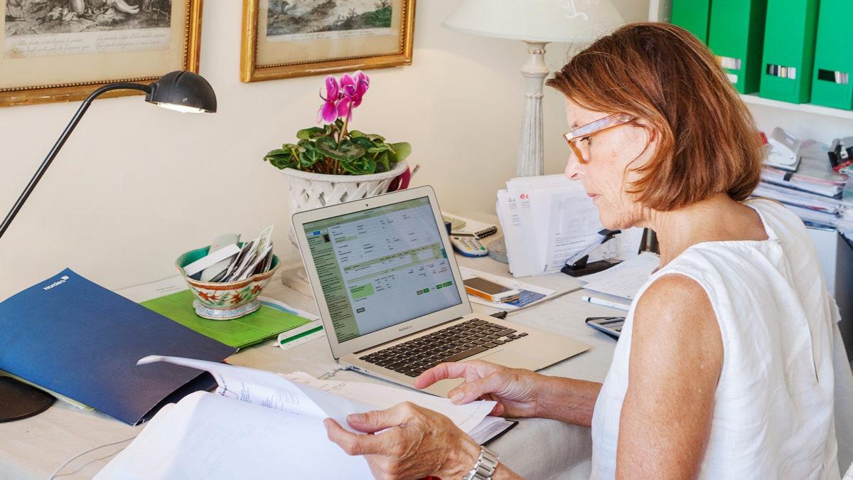 kvinna i ärmlös vit blus sitter vid skrivbord med dator, pärmar och mycket papper framme.