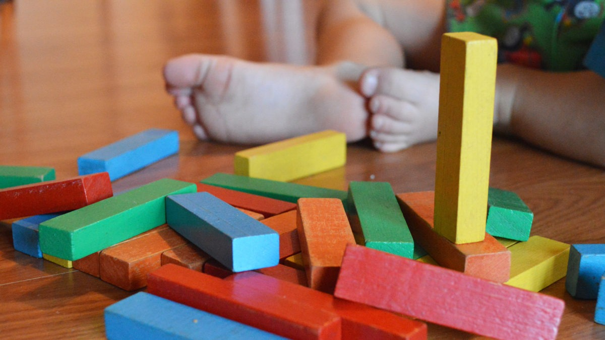 närbild å träklossar i olika färger utspridda på ett golv. bakom dem fötterna på ett litet barn.