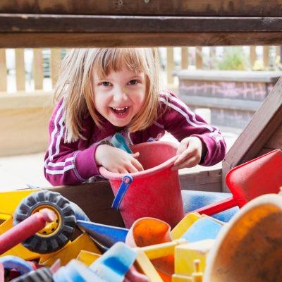 en liten flicka tittar fram under locket på en låda full med hinkar och spadar. Förskolemiljö utomhus i bakgrunden.