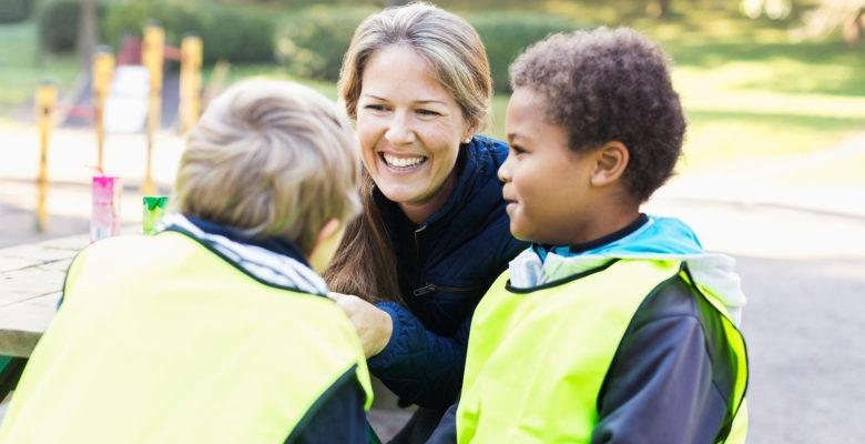 närbild å leende förskollärare med två förskolebarn i gula västar. Utomhus i förskolemiljö.