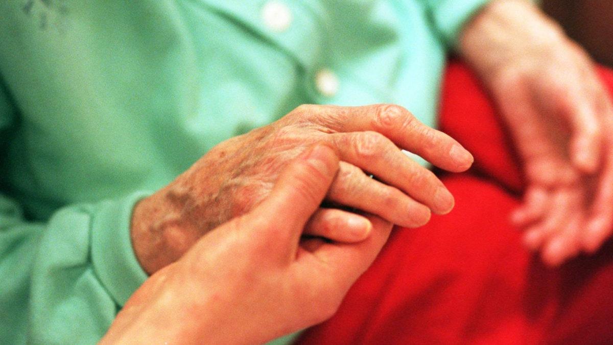 Händer mot ett rött täcke i en säng. En yngre person håller i en äldre persons ena hand.