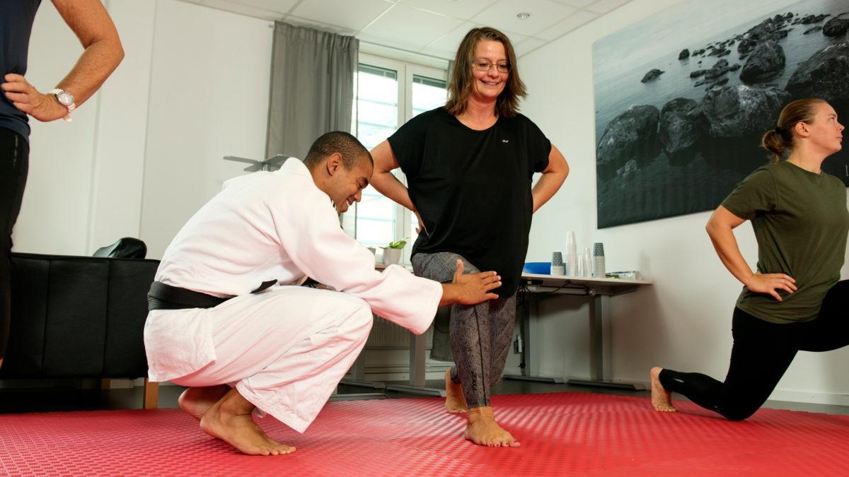 en judoinstruktör i vit dräkt står på huk och instruerar en knästående kvinna i träningskläder