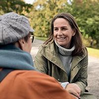 Två kvinnor samtalar utomhus, tema återhämtning.