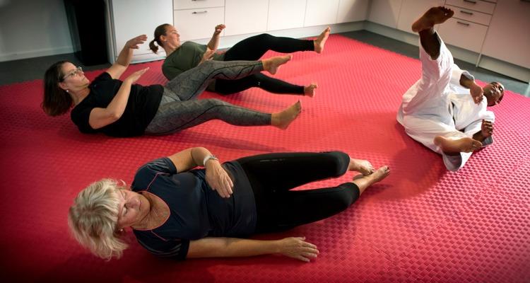 en grupp träningsklädda kvinnor och en judoklädd instruktör ligger på en röd matta.
