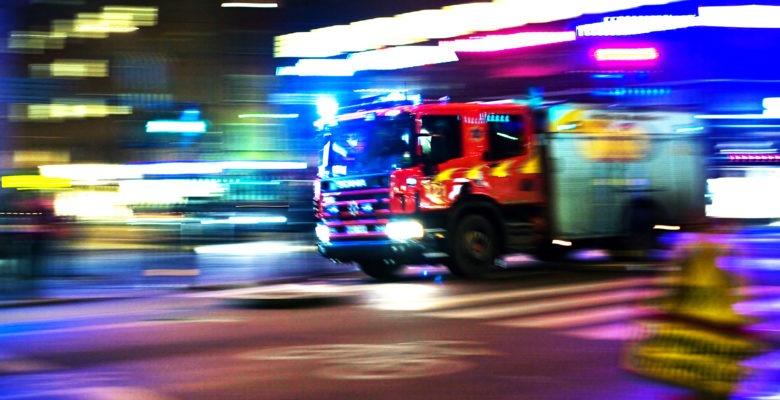 En brandbil under utryckning i mörker. Långa linjer av ljus visar att det går fort.