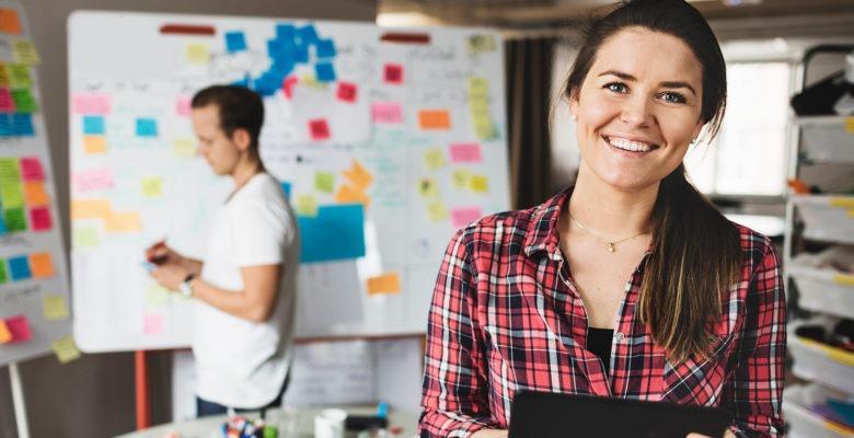 Kvinna i rödrutig skjorta och mörkt bakåtstruket hår, ler in i kameran. I oskarp bakgrund en man i t-shirt. Båda står framför en tavla med färgglada post-it-lappar.