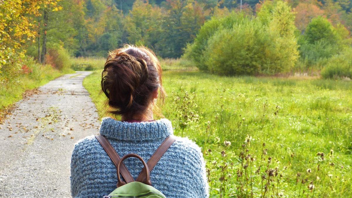 ryggren på en kvinna i grå ylletröja och brunt uppsatt hår, på en grusväg i vackert öppet höstlandskap med ängar och skog.