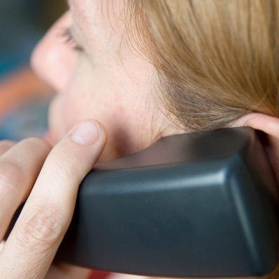 kvinna i rött hår talar i telefon. sedd snett bakifrån.