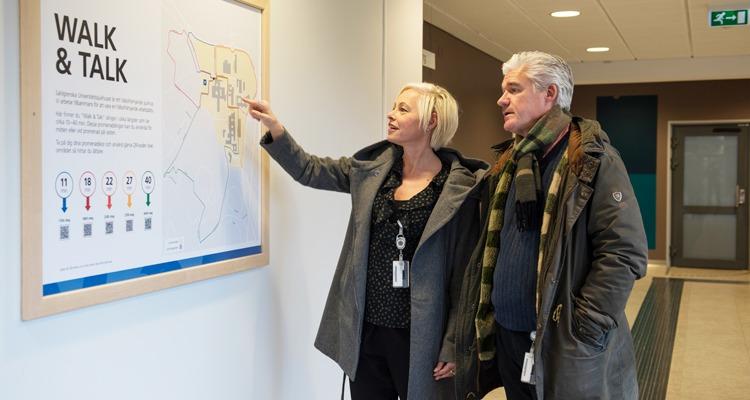 walk and talk tavla i netrén till Östra sjukhuset, Göteborg. Britt-Marie Zaman och Ingemar Blomqvist står intill tavlan och tittar på den.