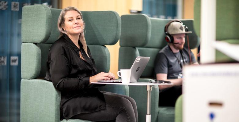 En öppen kontorsmiljö, En kvinna och en man sitter i fåtöljer och arbetar på bärbara datorer .