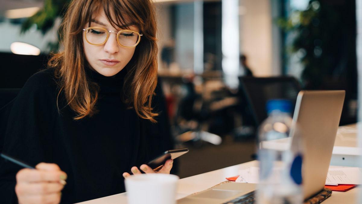 Porträtt av allvarlig kvinna i brunt hår och glasögon, som sitter och arbetar i kontorsmiljö.