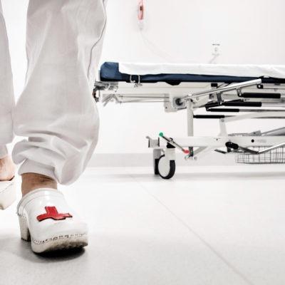 Träskobeklädda fötter och sjukhussäng, i en sjukhuskorridor.