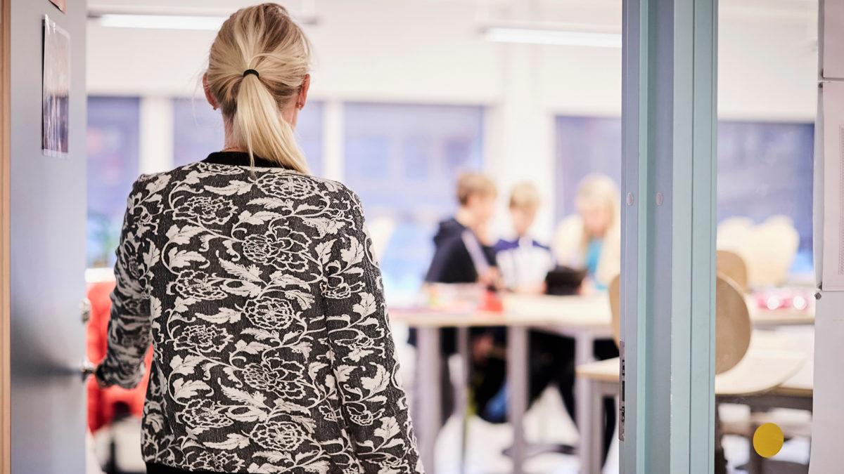 kvinnli lärare går in i klassrum, syns bakifrån. Hot och våld ny rapport AFA Försäkring.