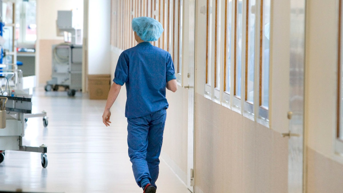 sjukhuskorridor där en person går bort från kameran, klädd i blå operationskläder. Tema vinterkräksjuka.