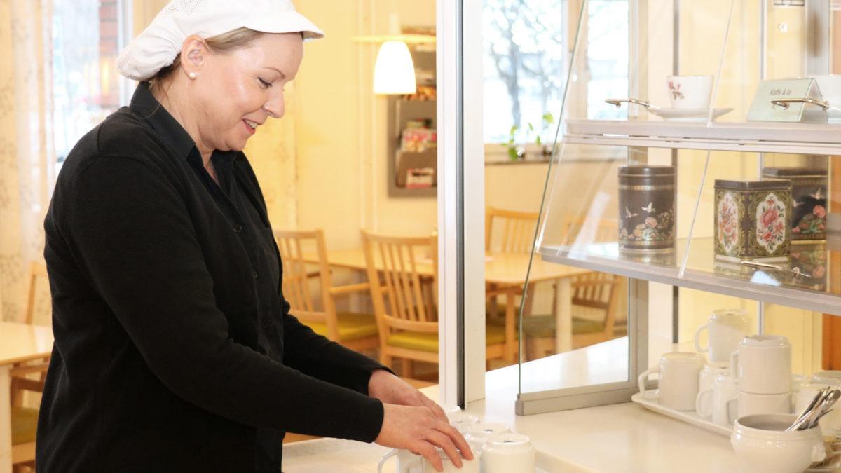 Pernille Seibaek, språkombud vid kostenheten i stadsdelen Årsta-Enskede-Vantör. Hon står i profil och ordnar några muggar, på en bänk i den restaurang där hon arbetar.