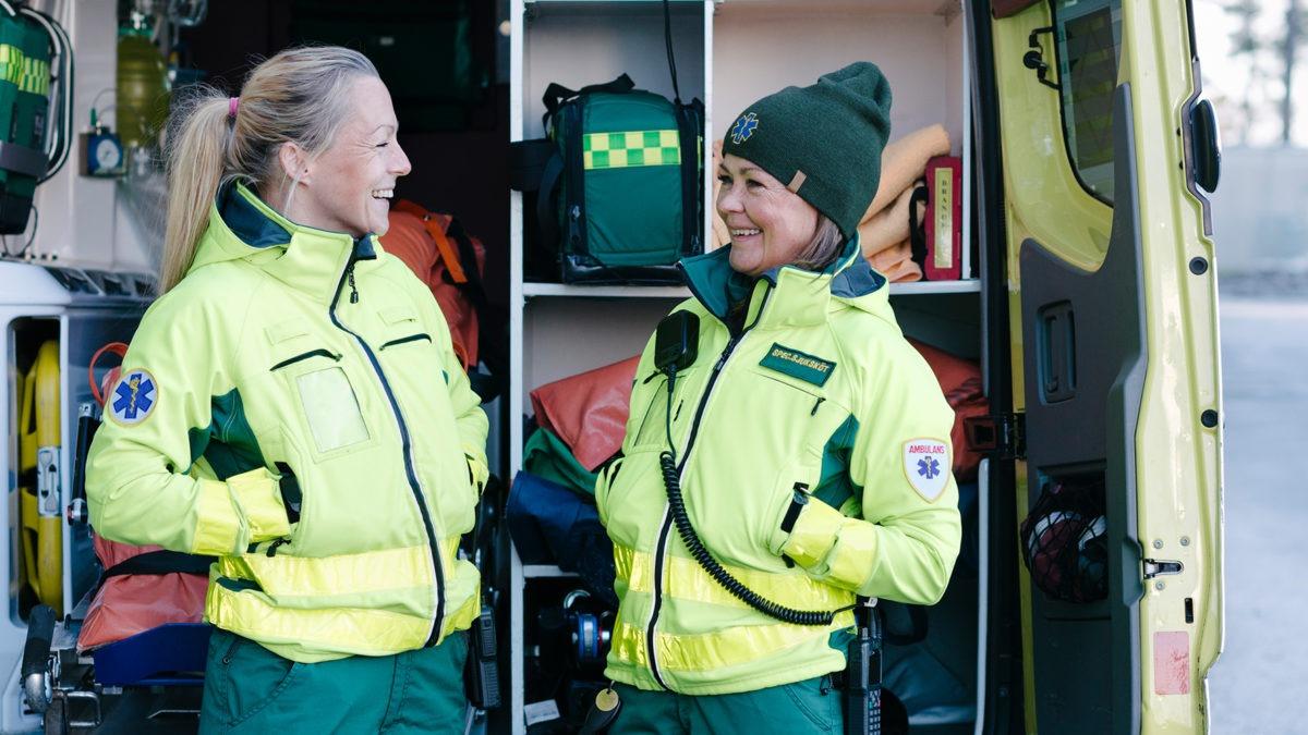 två kvinnliga ambulansförare står mitt emot varandra utanför en ambulans. De ler mot varandra. I bakgrunden syns den öppna ambulansen full med utrustning.