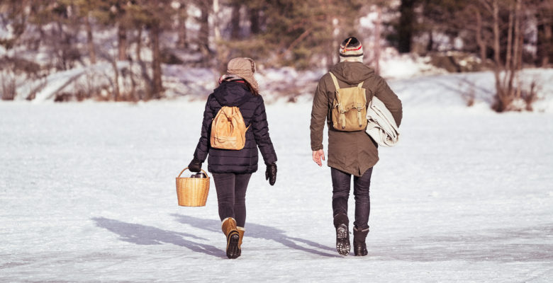 vinter. Två personer går med ryggen mot kameran, på isen, i sol. ryggsäckar och kaffekorg.