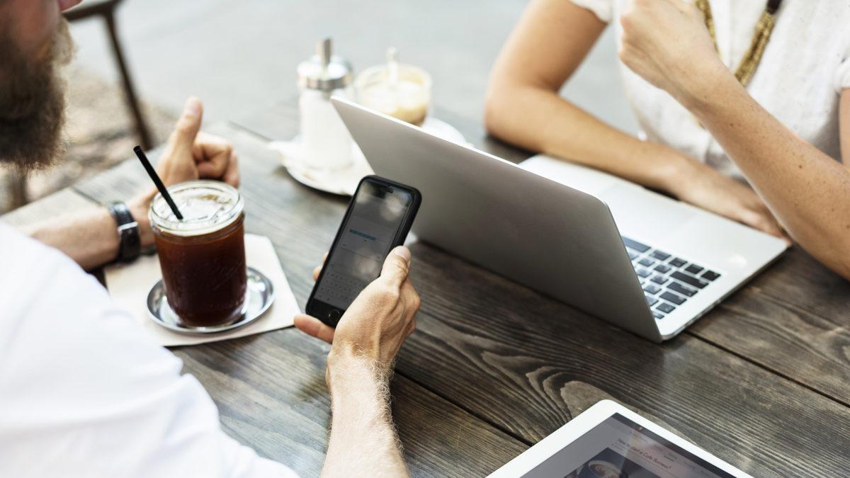 En man och en kvinna vid ett träbord, med dator och mobil och kaffe. Man ser armar och händer men inga ansikten.