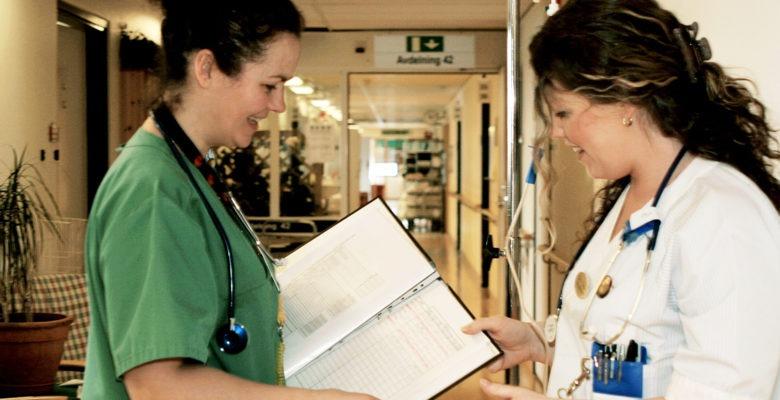 två sjuksköterskor i profil står i en sjukhuskorridor mitt emot varandra. Den ena är på väg att lämna över en pärm till den andra. De ser glada ut.