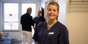 Porträtt på Viktoria Andersson, rehabkoordinator på Gävle Strands hälsocentral. Viktoria har en märk sjukhusblus på sig och står i en korridor på hälsocentralen, med ett par personer i bakgrunden.