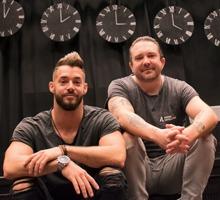 Två män sittande på scenkant i ungdomshus.