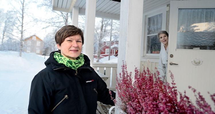 Kvinna från hemtjänst framför farstu, tema Vård i annans hem.