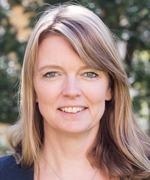 närbild på Marie Härstedt, HR-chef i Lomma kommun. Marie har långt hår och står utomhus med ett grönt träd skymtande i bakgrunden.