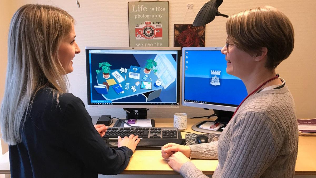 Två kvinnor står vid ett skrivbord med datorskärmar och spelar Helsingborgs stads datorspel om medarbetarskap, tema gamification.