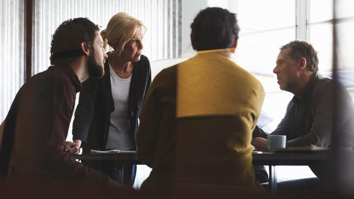 fyra vuxna personer runt ett bord pratar med varandra. Motljus från ett fönster bakom dem.