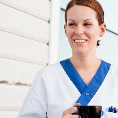 två kvinnor sjukhuskläder står utomhus mitt emot varandra. Den ena kvinnan har en kaffemugg, den andre ett äpple i handen. De ler mot varandra.