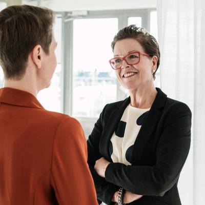 Två kvinnor står framför ett fönster i ett rum och samtalar.