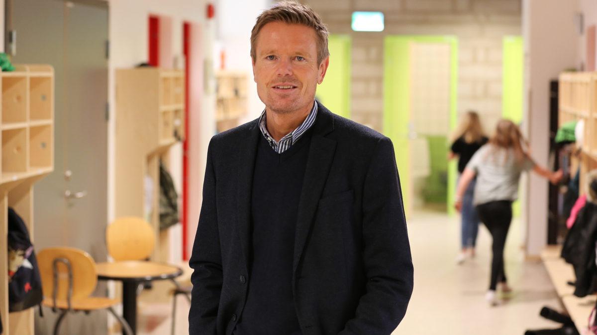 porträtt av Jonas Hällström, rektor på Fladängskolan i Lomma komun. Bilden tagen i en skolkorridor med springande barn bakom honom.
