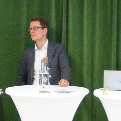 Paneldebatt på Forte med representanter från arbetsmarknadens parter. Framför ett grönt draperi står fyra personer vid höga vita bord.