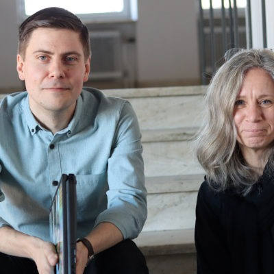 Seabstian Söderström, HR-samordnare och Tatjana Mineur, HR-chef i Gnesta, sitter i en stentrappa i kommunhusmiljö.