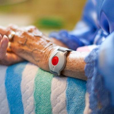 Närbild av en äldre människas händer som vilar i knäet. Personen har ett larm runt handleden.