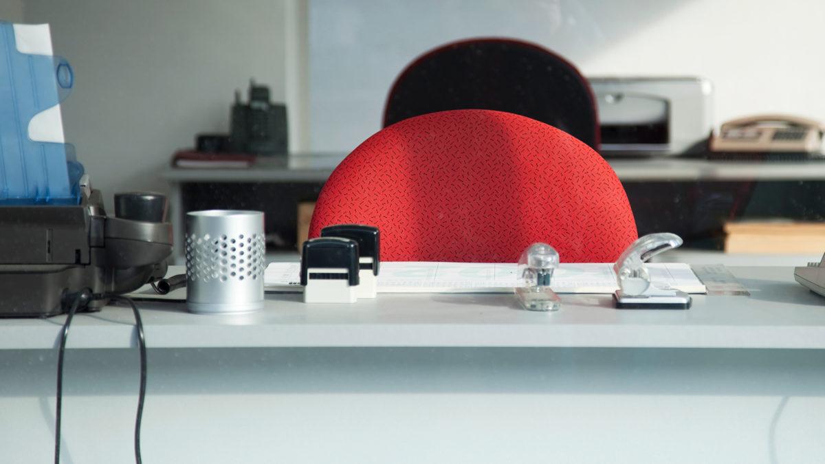 ett vitt tomt skrivbord med röd stolsrygg, sett framifrån.