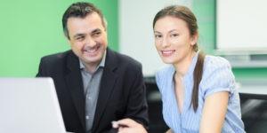 en man och en kvinna vid ett skrivbordmmed en dator framför sig. Mannen tittar förtjust på kvinnan. Kvinnan är yngre och ser in i kameran, leende.